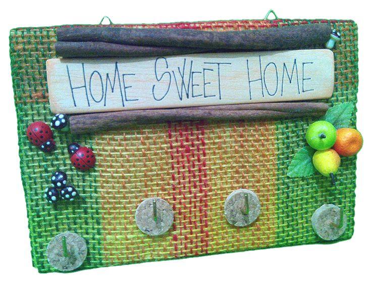 """Pannello appendi oggetti.Pannello rigido, rivestito in juta colorata. Ganci portaoggetti. Colorati decori """"frutta"""", sughero e funghetti, coccinelle e vere stecche di cannella. Grafica su legno naturale."""