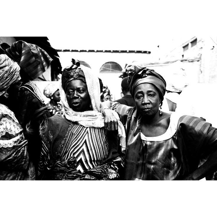 Sguardi Furtivi. Opera dell'archivio dell'agenzia DFP, fondata da Dani Maria Turriccia nel 1963. La fotografia appartiene a un reportage, condotto in Nigeria nel 1975. Due splendide donne, vestite con abiti tradizionali, sembrano invitarci alla festa. I muri delle case spariscono, assorbiti dalla luce abbagliante del sole.  Africa, Nigeria 1975.
