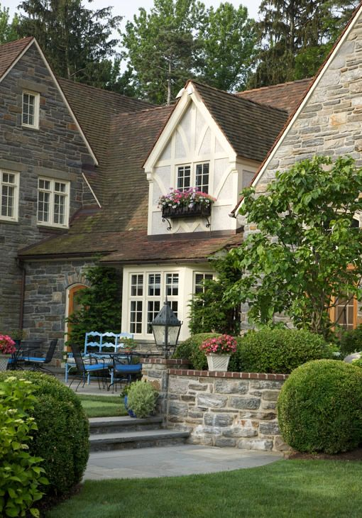 Beautiful... I love the stone walls, the round hedges, the Tudor style home, the lantern, the flagstone patio, and the window flower basket.