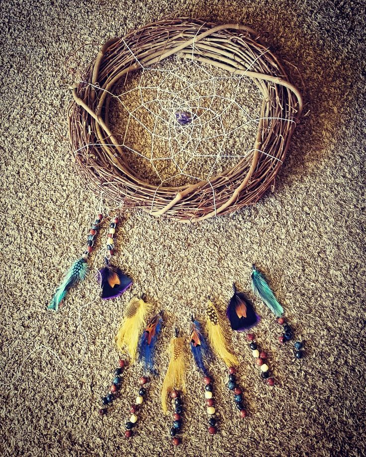 Beautiful traditional native american style wreath dreamcatcher with an amethyst stone in the center. Colored pheasant feathers and dyed wood beads decorate the bottom. Will soon be for sale at DreamWeaver.