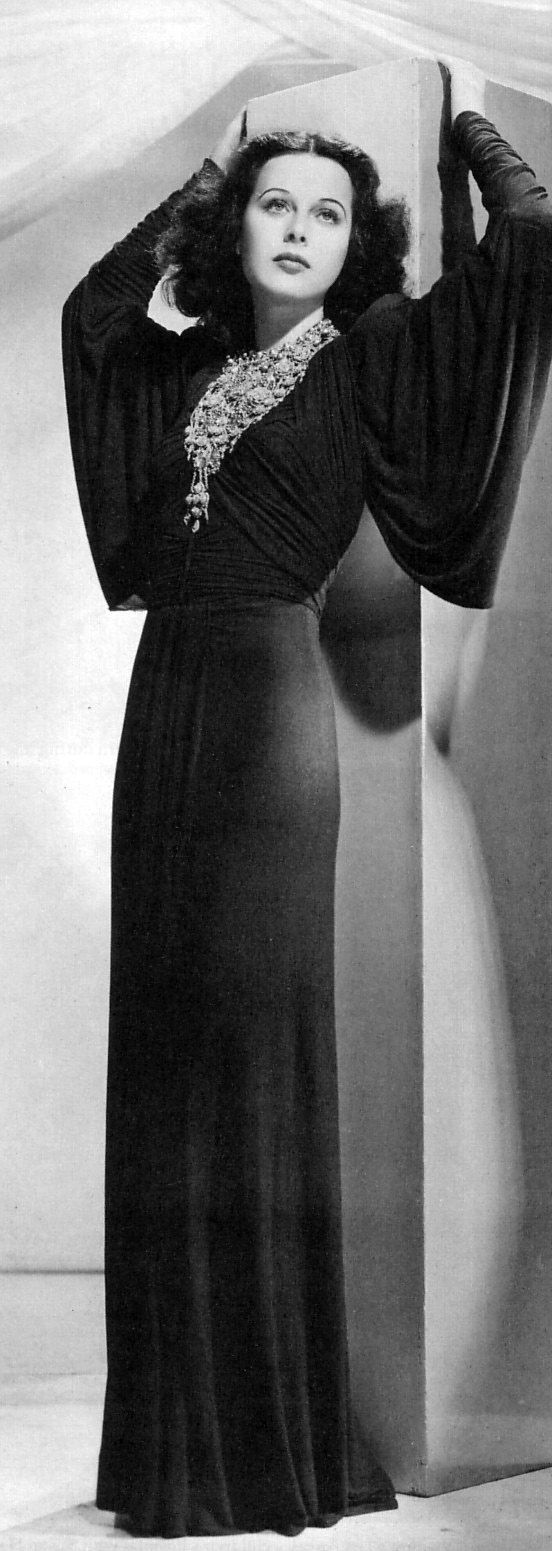 Hedy Lamarr in a statement necklace and crepe gown with dolman sleeves.