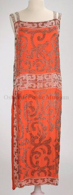 1920 calf-length straight-cut sleeveless dress of coral-colored silk crepe with gold and white bead decoration; square neckline with two shoulder straps on each side; right side only of dress from hip to hem is a fabric panel of narrow pleats set in. Label located on back neckline, white cloth with golden-yellow machine embroidery: Made in France/RUE DE LA PAIX GOWN/PARIS.