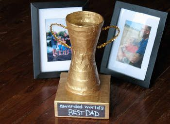 Trophy for Dad -FATHERS DAY  What you'll need:        2 foam coffee cups      5 inch square box (or one cut to size)      Masking tape      1 gold chenille stem      Gold craft paint      Black construction paper, cut to fit on side of box      White paint pen      Scissors      Paintbrush      White craft glue