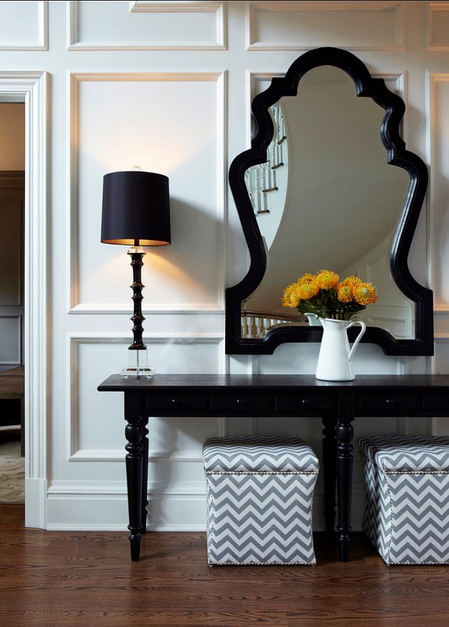 """Foyer Ideas. Beautiful foyer furniture ideas A large black stained console was used with tall glass buffet lamps and an oversized sculptural mirror set above the wall paneling.  Console table is from Pottery Barn. The mirror is from """"Noir"""" in LA, and lamps are """"Pacifica"""" Buffet Lamp"""" from Horchow. #Foyer #EntrywayDesign"""