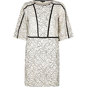 Witte jurk met gebloemd kant en wijduitlopende mouwen