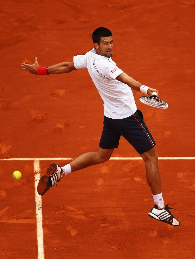 PARIS, FRANCE - JUNE 05: Novak Djokovic of Serbia plays a volley in his men's singles quarter final match against Jo-Wilfried Tsonga of France during day 10 of the French Open at Roland Garros on June 5, 2012 in Paris, France. (Photo by Clive Brunskill/Getty Images)