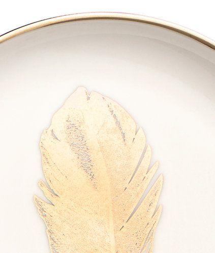 Vit/Fjäder. En liten tallrik i porslin med guldfärgad kant och tryckt fjädermotiv. Diameter 12,5 cm.