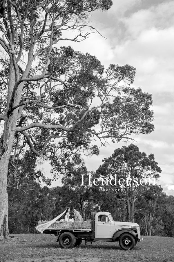 Bride and Groom sitting on the back of an old flat bed truck. https://www.facebook.com/HendersonPhotographics