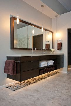 Master bathroom vanity with river rock accent and concealed medicine cabinets at each end of mirror.