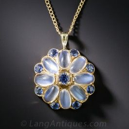 This lustrous jewel really got around: 8 celestial gemstones (a.k.a. blue-flash moonstones) are embellished with electric blue, decidedly earthbound gems (from Montana - Yogo Gulch to be more precise) in this enchanting flower pendant dating back to the early-twentieth century. Hand-fabricated in 15ct. rosy-yellow gold, hence very likely of British origin! 7/8 inch diameter, the new chain measures 18 inches.