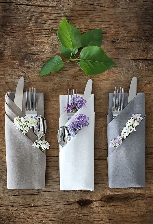Flowers tucked into folded napkins