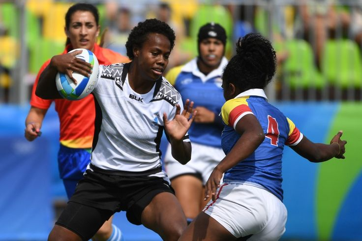 Fiji's Raijieli Daveua (L) hands off Colombia's Khaterinne Medina in the womens rugby sevens match between Colombia and Fiji during the Rio 2016 Olympic Games at Deodoro Stadium in Rio de Janeiro on August 7, 2016. / AFP / Pascal GUYOT
