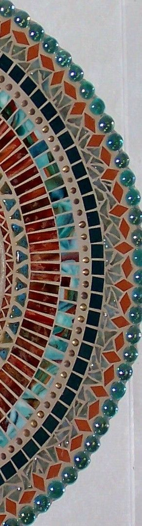 This mosaic mirror was created using teal, aqua, adobe, and deep red/orange (rust) stained glass, glass gems, upholstery nails, and ceramic beads. This piece measures 24 across and has an 11 mirror. Its sealed and the hanging hardware is attached. Ive signed and dated it on the back.