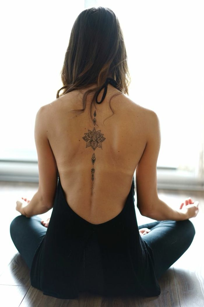 lotus flower tattoo, brunette woman sitting in lotus position, with an open back black top, and blue jeans, with lotus tattoo, outlined with black in on her back