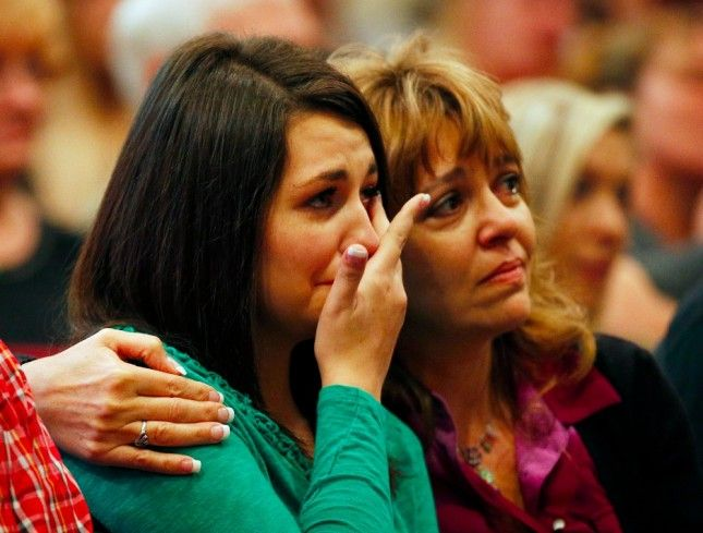 Lacey Scroggins, left, is comforted by her mother Lisa Scroggins during a church service at the New Beginnings Church of God, Sunday, Oct. 4, 2015, in Roseburg, Ore. (AP Photo/John Locher)
