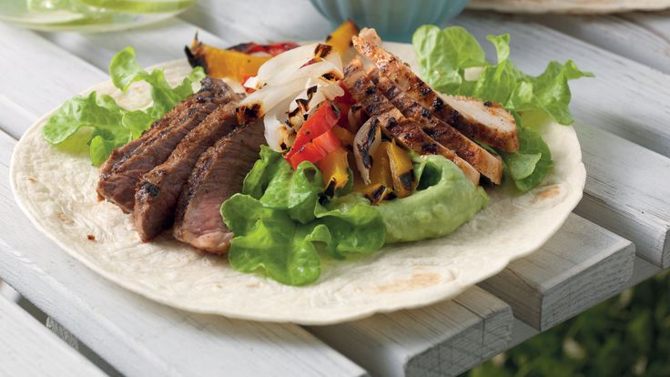 Fajitas fyllda med flankstek, grillade grönsaker, krämig guacamole, gräddfil och färsk koriander.