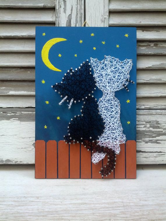 This wooden decoration with two kittens on a fence at night made from black and white string and nails and balsa wood on a black painted wooden piece