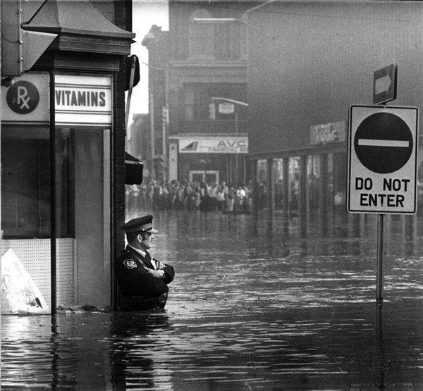 Police officer guarding Galt, Ontario pharmacy in waist-high flood waters, 1974