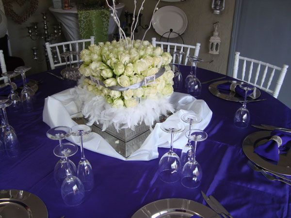 A square of white roses surrounded by a white feather boa with white willow sticks in the centre www.iceevents.co.za
