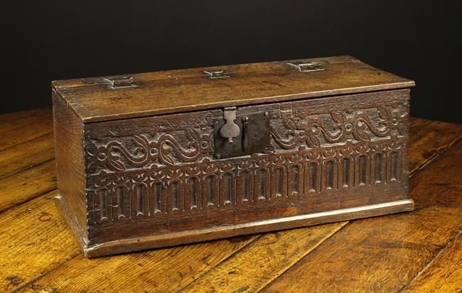 A 17th Century Boarded Oak Desk Box of rectangular form. The lid on iron butterfly hinges. The front board carved with a frieze of foliate strap-work above a band of nulling and having an iron hasp and lockplate, 10 in (26 cm) high, 25 in (64 cm) wide, 11½ in (29 cm) deep.
