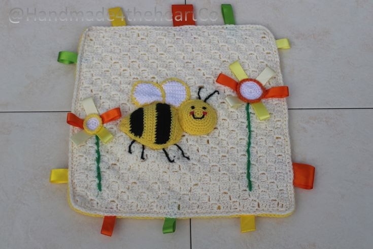 Crochet baby taggie blanket with bright bumble bee design.