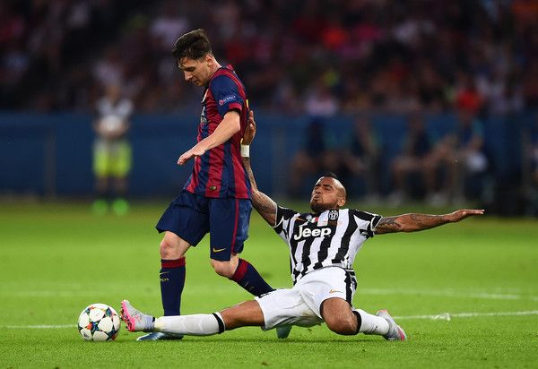 Lionel Messi of Barcelona is tackled by Arturo Vidal of Juventus during the UEFA Champions League Final between Juventus and FC Barcelona at Olympiastadion on June 6, 2015 in Berlin, Germany.