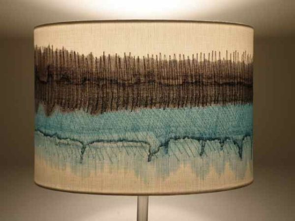 Handmade Lampshades add a touch of elegance to any interior. Inspired by the far reaching horizons over the Yorkshire moors, these handmade lampshades are created on soft white linen. The cloth is hand painted with free flowing colour which suggests the shape and structure of the horizon: the bands of colour merge and flow. Energetic machine stitch/Free Machine Embroidery creates further movement on the surface of the linen and mimics the sway of the reeds and grasses but maybe even the o...