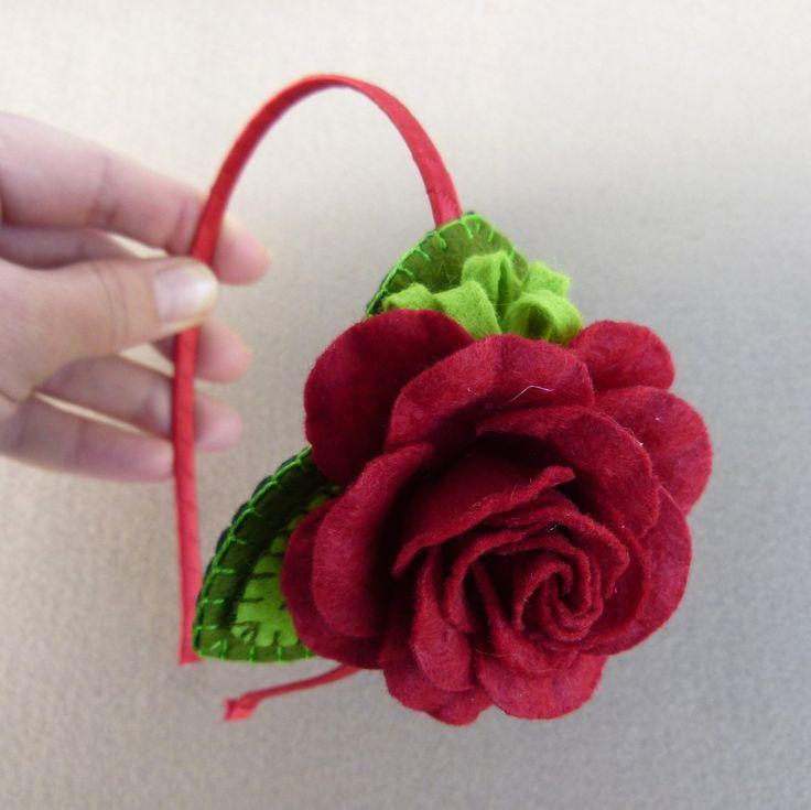 Čelenka do vlasů Čelenkado vlasů je ušita z extra silné a kvalitní plsti, doplněná tvarovanou růží z plsti.Vyšívaná částje připevněna na kovovou čelenku, omotanou saténovou stužkou. Rozměrozdobné části:7x7 cm, výška růže 3 cm