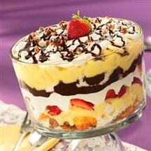 Banana Split Trifle. 	3 cups cold milk  •	1 (5.1 oz.) box vanilla or cheesecake flavored instant pudding mix  •	1 (8 oz.) can crushed pineapple, drained  •	1 prepared angel food cake, cut into cubes  •	1 cup strawberries, sliced  •	1 (8 oz.) container frozen whipped topping, thawed  •	1 medium firm banana  •	1/4 cup pecans, chopped  •	12 ounces Smucker's® Hot Fudge Microwaveable Topping