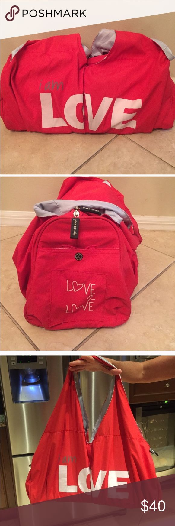 """Peace Love World duffle bag Red nylon duffle bag. Peace, Love , World... """"I am Love"""".  2 long straps.  7 pockets total.  18 inches by 8 inches.  Great for travel!! Peace Love World Bags Travel Bags"""