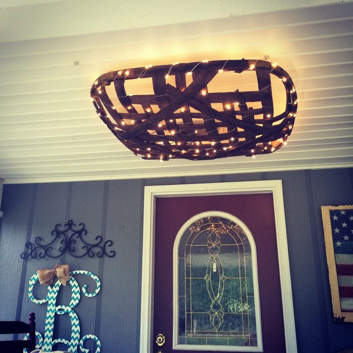 Tobacco basket wrapped with miniature lights and suspended above the door on a covered porch.