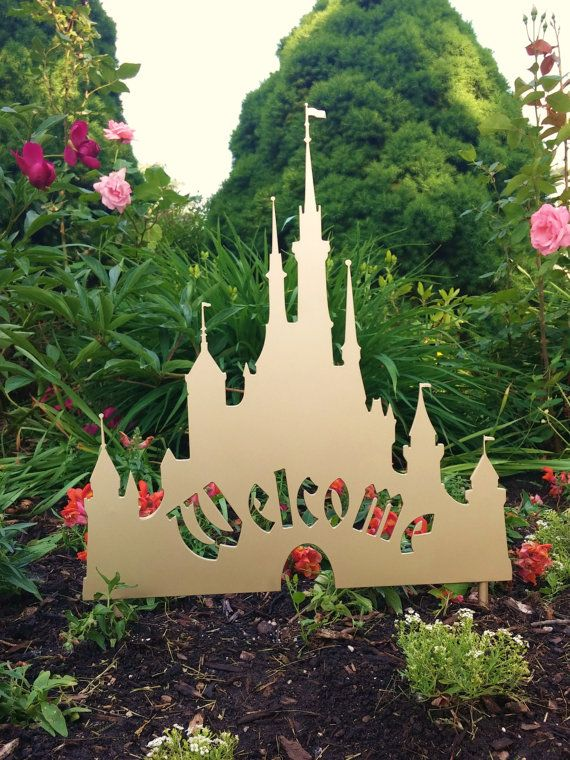Give your yard or garden the royal treatment with this beautiful Disney inspired Castle Welcome Sign. Dimensions: 16 Wide - 17 Tall  This work of art is inspired by Cinderellas Castle from Walt Disney World. Each sign is plasma cut from 11 gauge STEEL so it is built to last! The 3/8 thick stakes that are welded to the back will insure your beautiful sign stays in place. Select from a variety of finishes. - PICTURED is the metallic gold finish  NATURAL STEEL - Unfinished steel plate with a…