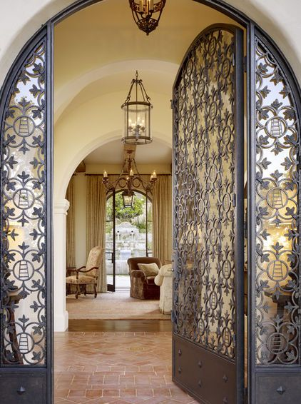 Love the idea of having an iron and glass front door. Except, I would change the glass to white stained glass so that outsiders cannot see into the house through the front door. Also, I like this door idea for the arch patio double doors that will lead to the patio area and back yard.Love the floor tile in this picture too. I like the entry way, as well. Small foyer then living area.