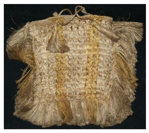 Fine flax weave Māori kete with complex decorative elements on both sides and a thick fringe along three edges. Attached to the handles are two tassels on each side.