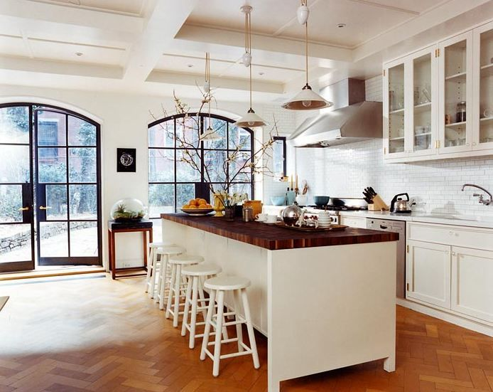 white open kitchen with butcher block countertop herringbone wood floor huge arched multi paned glass doors and window two white pendant - Kitchen Cabinets New York City
