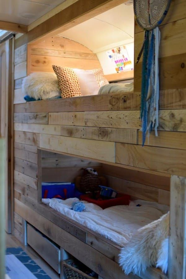 The parents' bed converts into a play area during the day. There are bunk beds along the wall for the kids, and a crib for the baby.