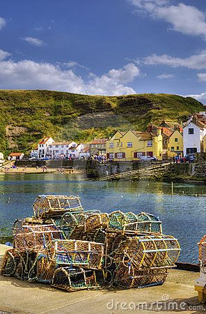 Scenic view of Staithes harbor and waterfront with lobster pots in foreground, North Yorkshire, England.