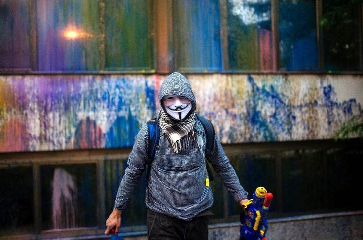 A protester wearing a Guy Fawkes mask sprays paint with a toy water gun on Macedonia's Public Revenue Office headquarters in Skopje as part of a series of protests that have been dubbed the