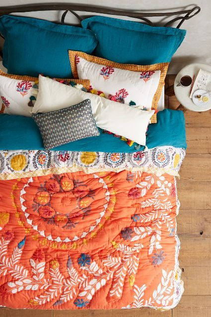 Spotted at Anthropologie: Bright colors such as this Tangerine quilt create a bohemian inspired bedroom with Blue Paisley sheets and pillows #PPGColorTrends