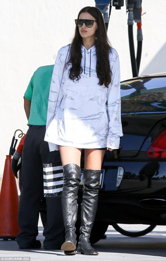 Stunner: The Russian beautywore a long hoodie as a dress and paired it with over-the-knee shiny black leather boots and a pair of giant sunglasses