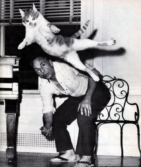George Balanchine, choreographer, admiring the work of his cat, Murka.
