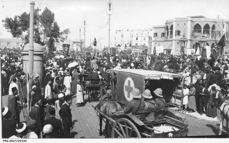 A street scene, possibly in Cairo, Egypt showing crowds watching a parade  of horse-drawn vehicles and a motor ambulance