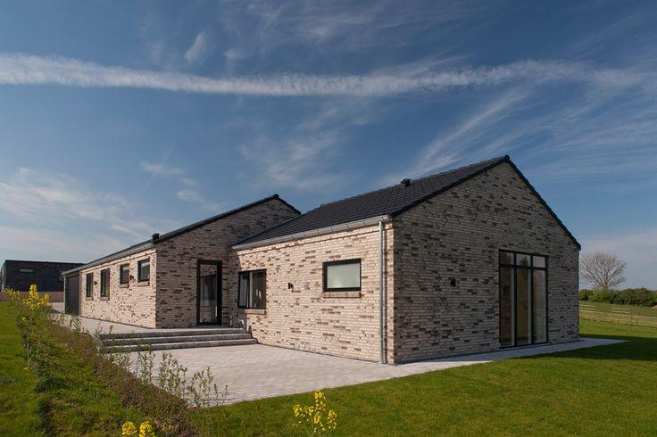 Forskudt tagkonstruktion med mursten i  flere nuancer af brun, sorte betontagsten og sorte træ/aluvinduer.