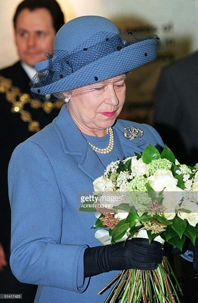 Queen Elizabeth receives flowers after arriving at the Commonwealth Institute in London 24 February. The Queen, patron of the British Red Cross society, presented a new Royal Charter after the group unified into one society. The Queen earlier heard the news that her sister, Princess Margaret, suffered a stroke on the Caribean island of Mustique. (Photo credit should read ADRIAN DENNIS/AFP/Getty Images)