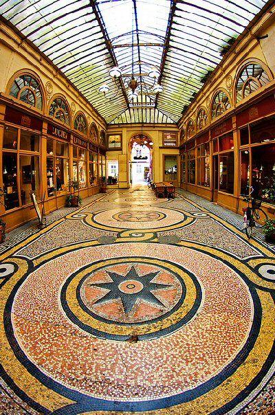 galerie Vivienne - Paris 2ème La galerie est construite en 1823 par le président de la Chambre des Notaires Marchoux, à l'emplacement des hôtels Vanel de Serrant et du passage des Petits-Pères, d'après les plans dessinés par l'architecte François Jean Delannoy. Ce dernier conçoit un décor de style pompéien néo-classique recouvert d'une verrière élégante, fait de mosaïques, peintures et sculptures exaltant le commerce.