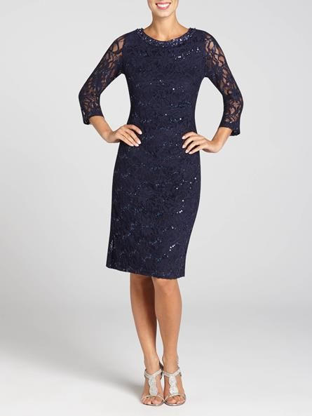 Laura. Round embellished neck. Sheer 3/4 sleeves. Sequined lace throughout. Knee-length. Back zip with hook