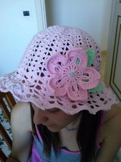 Cappello in cotone rosa con fiore e foglie verdi