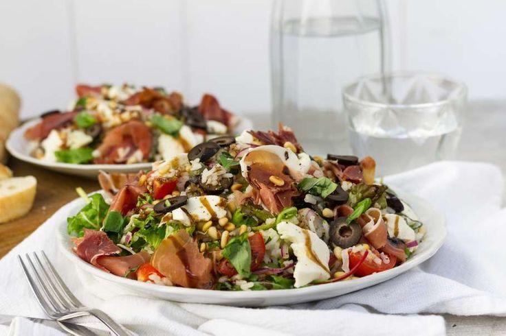 Recept voor zomerse rijstsalade op Italiaanse wijze voor 4 personen. Met zout, olijfolie, peper, slamelange, cherrytomaat, pijnboompitten, prosciutto, ciabattabroodje, rijst, zwarte olijven, basilicum, mozzarella, rode ui, kappertjes en balsamicoazijn
