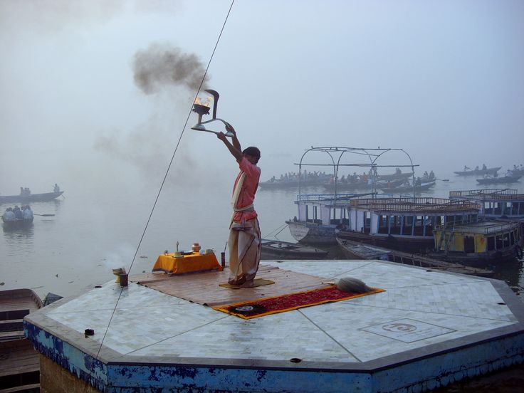 Hindu priest offering prayers to the elements of nature at the banks of the river Ganges - Varanasi, Uttar Pradesh, North India