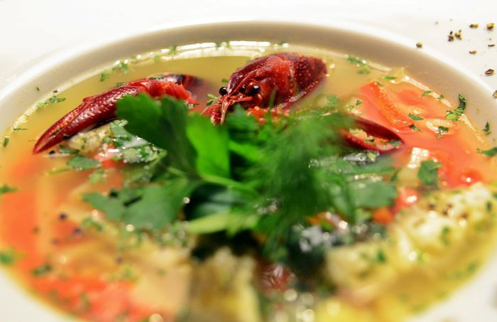 Fish Soup in the form of delicate Baltic salmon and zander stock with vegetables – and with a crayfish, important for the flavour and cooked whole.